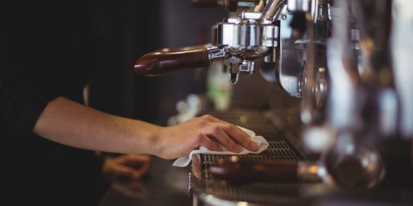 Mid section of waitress wiping espresso machine with napkin in café